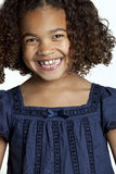 Little girl laughing out loud. Happy little girl with frizzy hair is laughing out loud and looking into the camera, showing her teeth that are changing Stock Photo