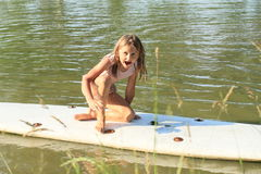 Little girl laughing on surf board Royalty Free Stock Photo