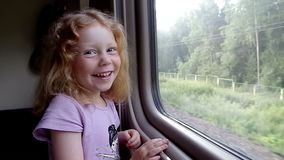 Little girl laughing at the train window stock video footage