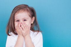 Little girl laughs covering her face with her hands stock photo
