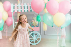 Little girl laughs in a studio decorated many balloons Royalty Free Stock Image