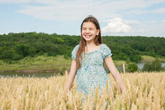 Little girl laughs on the wheat field Royalty Free Stock Image