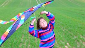 Little girl launches a kite in a field in spring.