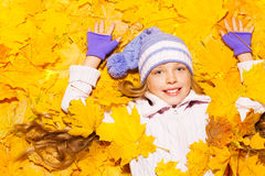 Little girl lay in autumn maple leaves Stock Photo