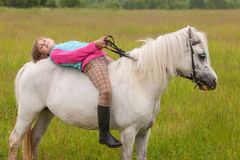 The little girl lay on her back white horse  Royalty Free Stock Images