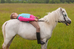 The little girl lay on her back white horse Stock Photos