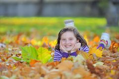 Little girl laying on autumn leaves Royalty Free Stock Image