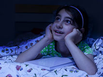 Little girl laying in bed daydreaming, Stock Images
