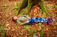Little girl laying on the bed of leaves in national park Biograd Stock Images