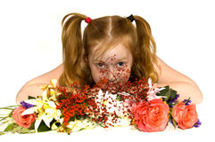 Little girl laying behind some flowers. On white Stock Image