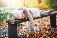 Little girl laying on bench in forest Stock Photography