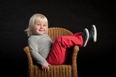Little girl laying in a cane chair Stock Image