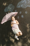 Little girl laying down on asphalt after drawing with chalk. Little girl laying down on asphalt with umbrella after drawing clouds with rain drops with chalk Stock Image