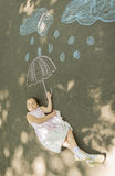 Little girl laying down on asphalt after drawing clouds with rain drops and umbrella with chalk. Concept of child imagination Royalty Free Stock Photos
