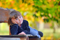 Little girl laying down on a bench Stock Images