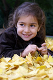 Little girl laying down over autumn leaves. Little girl smiling laying down over autumn yellow leaves Stock Photos