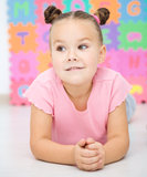 Little girl is laying on floor Royalty Free Stock Photography