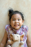 Little girl laying on floor with elephant doll Stock Photo