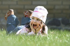 Little girl laying on grass Stock Images