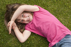 Little girl laying in grass Stock Image