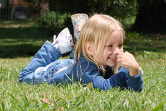 The little girl laying on a grass Royalty Free Stock Photography