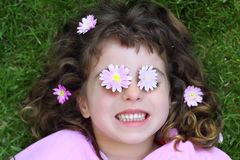 Little girl laying grass daisiy flowers in eyes Stock Image