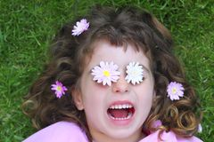 Little girl laying grass daisiy flowers in eyes Royalty Free Stock Images