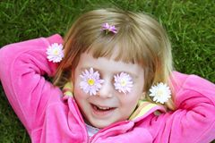 Little girl laying grass daisiy flowers in eyes Stock Images