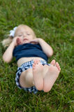 Little girl laying in the grass with feet in air Royalty Free Stock Image