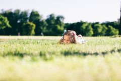 Little girl laying on the grass field and looking aside. royalty free stock images