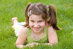 Little Girl Laying in the Grass Laughing Royalty Free Stock Photography