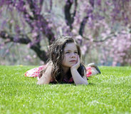 Little girl laying in the grass stock photo