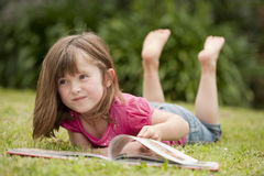 Little girl laying in grass reading Stock Image