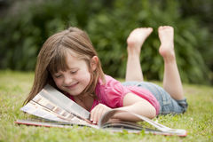 Little girl laying in grass reading Stock Images