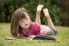 Little girl laying in grass reading Stock Photography