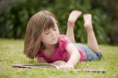 Little girl laying in grass reading Stock Photo