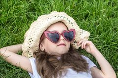 Little girl laying in the grass. summer time and sunny day. Little girl laying in the grass with sunglasses and summer hat. summer time and sunny day stock photo