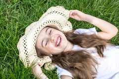Little girl laying in the grass. summer time and sunny day. Little girl laying in the grass with sunglasses and summer hat. summer time and sunny day royalty free stock images