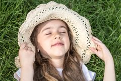 Little girl laying in the grass. summer time and sunny day. Little girl laying in the grass with sunglasses and summer hat. summer time and sunny day royalty free stock image