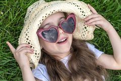 Little girl laying in the grass. summer time and sunny day. Little girl laying in the grass with sunglasses and summer hat. summer time and sunny day royalty free stock photos