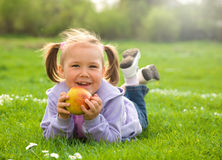Little girl is laying on green meadow Royalty Free Stock Photos