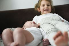 Little girl is smiling laying with her baby brother royalty free stock photos