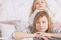 Little girl laying on her mom. Little girl laying on her angry mom on a bed royalty free stock photo