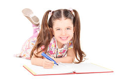 Free Little Girl Laying On The Floor And Drawing In Notebook Stock Photography - 38414292
