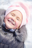Little girl is laying on a snow Royalty Free Stock Image