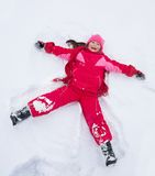 Little girl laying in star shape in snow Royalty Free Stock Image