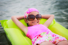 Little girl laying on tube swimming Royalty Free Stock Image