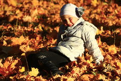Little girl laying in yellow leaves Stock Photography