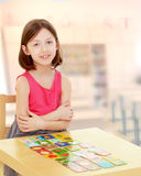 Little girl lays cards on the table Stock Photo