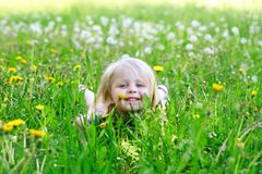 Little girl lays in dandelions outdoors Royalty Free Stock Photos